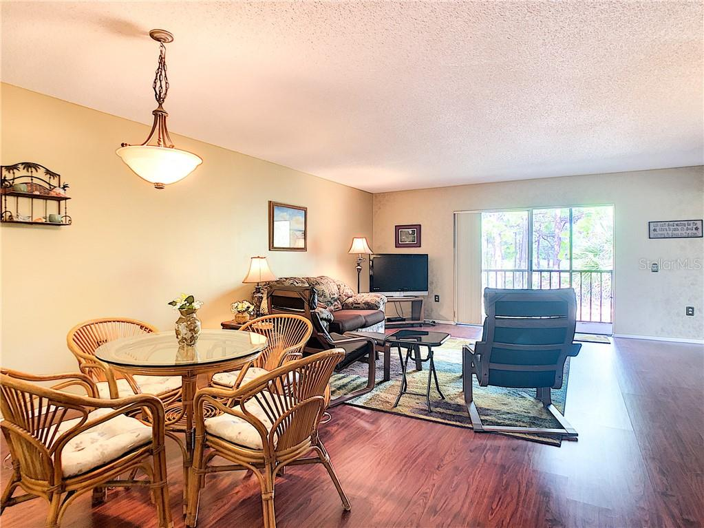 Dining and living area in great room with sliders to lanai - Condo for sale at 211 Rubens Dr #h, Nokomis, FL 34275 - MLS Number is N6103629