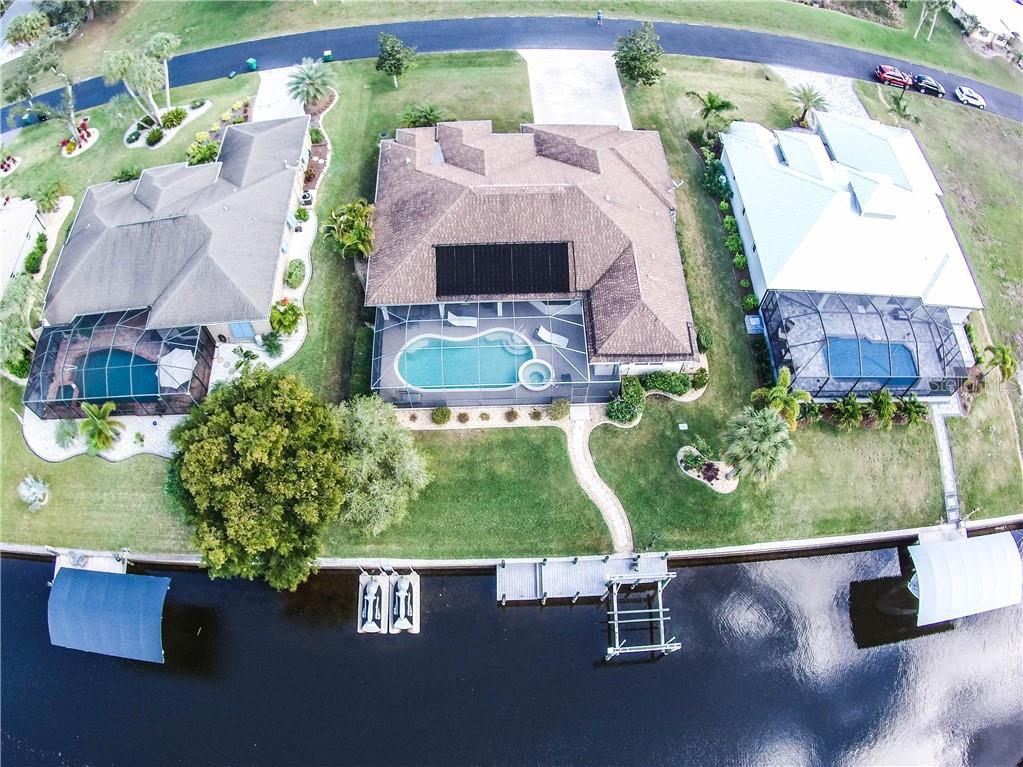 Aerial of home from the rear showing dock and pool area. - Single Family Home for sale at 2560 Pebble Creek Pl, Port Charlotte, FL 33948 - MLS Number is N6109100