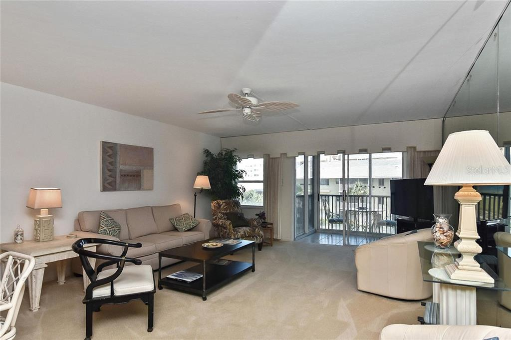 Living room with sliders to lanai - Condo for sale at 1150 Tarpon Center Dr #303, Venice, FL 34285 - MLS Number is N6110126