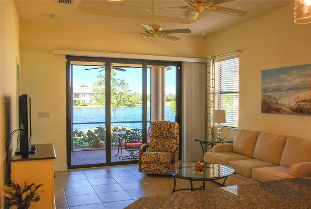 Great room with sliders to the lanai. Beautiful lake view - Single Family Home for sale at 10424 Crooked Creek Dr, Venice, FL 34293 - MLS Number is N6112285