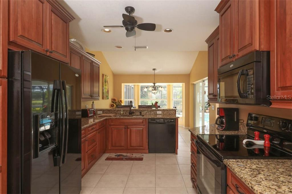 Rich cherry cabinetry and stone counters complete the kitchen. - Single Family Home for sale at 24620 Dolphin Cove Dr, Punta Gorda, FL 33955 - MLS Number is C7413467