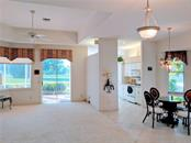 VIEW OF LIVING ROOM WITH TRAY CEILING, KITCHEN AND DINING ROOM - Single Family Home for sale at 26442 Feathersound Dr, Punta Gorda, FL 33955 - MLS Number is C7412660