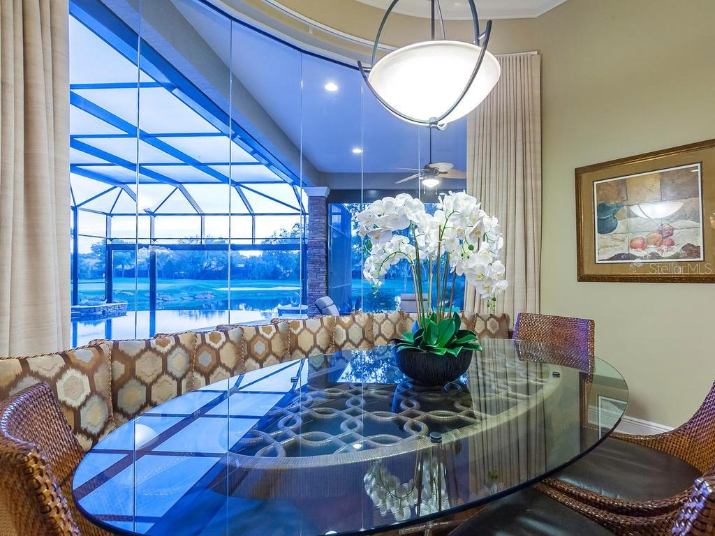A custom oval shaped casual eating space and banquet sits beneath the aquarium window. - Single Family Home for sale at 12312 Newcastle Pl, Lakewood Ranch, FL 34202 - MLS Number is A4403090