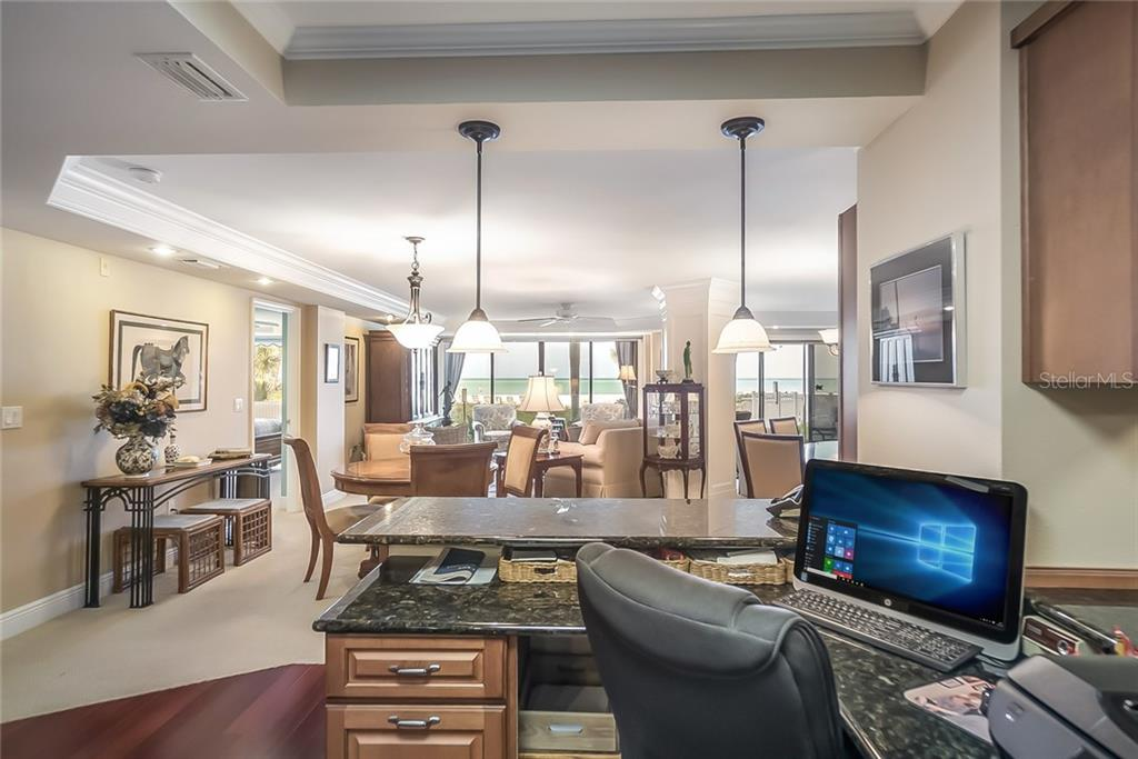 Built-in desk in kitchen w/Beach& Gulf views beyond dining/living area - Condo for sale at 20 Whispering Sands Dr #102 & 103, Sarasota, FL 34242 - MLS Number is A4441587