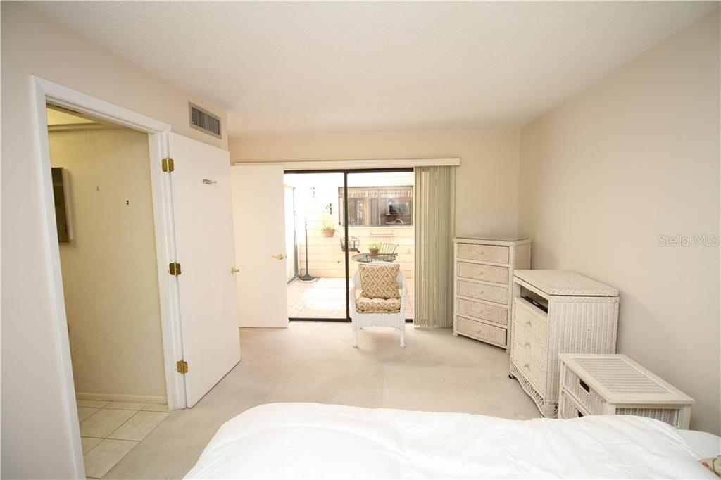 Downstairs master suite with courtyard view and en suite updated bathroom. - Townhouse for sale at 4319 Woodmans Chart #130, Sarasota, FL 34235 - MLS Number is A4445530