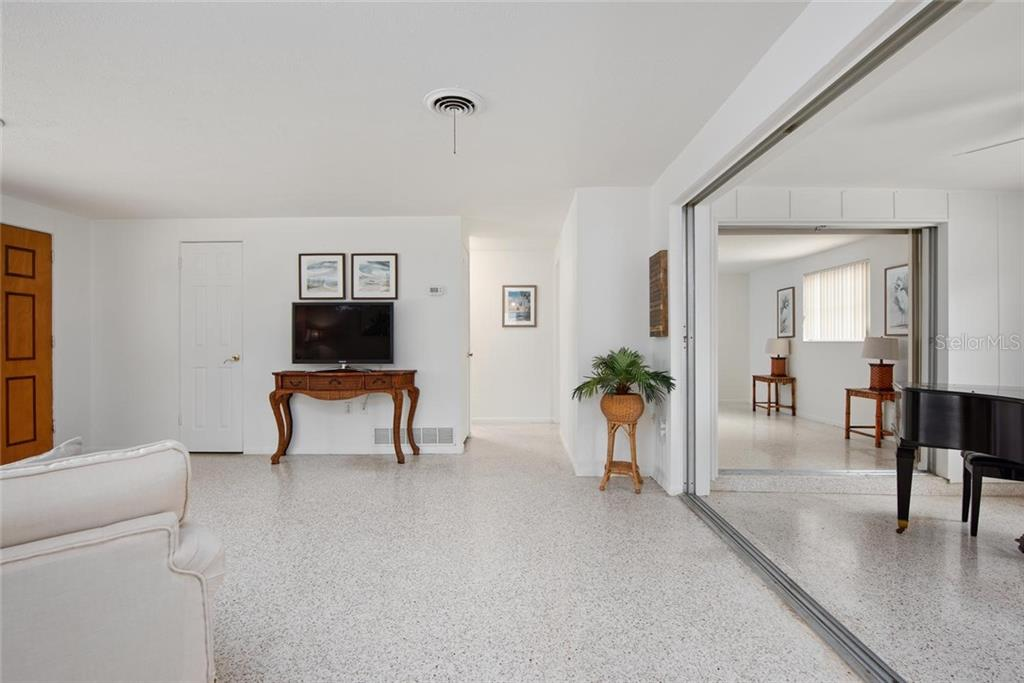 From the dining area, across the living area, you can see into the Florida room and into the master bedroom. - Single Family Home for sale at 691 Tarawitt Dr, Longboat Key, FL 34228 - MLS Number is A4451584